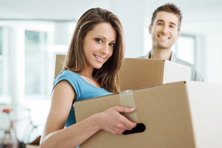 new beginning: Happy smiling couple moving in a new house and carrying carton boxes, relocation and renovation concept