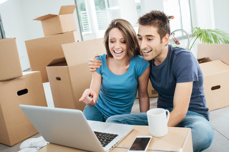 they are watching: Smiling couple sitting on their new house floor surrounded by carton boxes, they are watching a funny video on a laptop and laughing