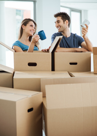 real estate: Happy couple having a coffee break during a relocation in their new house, they are holding a mug and smiling at each other