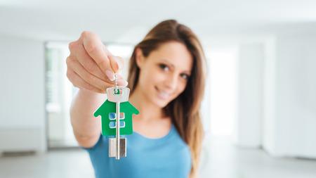 그녀의 새 집, 부동산 및 재배치 개념의 집 열쇠를 들고 아름 다운 웃는 여자