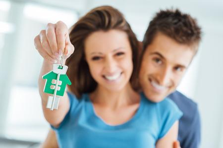 웃는 젊은 부부 새 집 열쇠를 들고, 부동산 및 재배치 개념