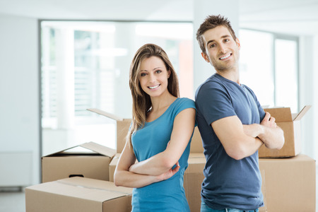 excited man: Smiling loving couple posing in their new house back to back surrounded by carton boxes Stock Photo