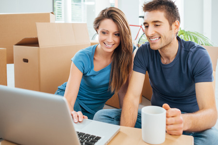 Happy couple sitting on their new house floor surrounded by carton boxes and using a wireless laptop during a coffee break Stock Photo
