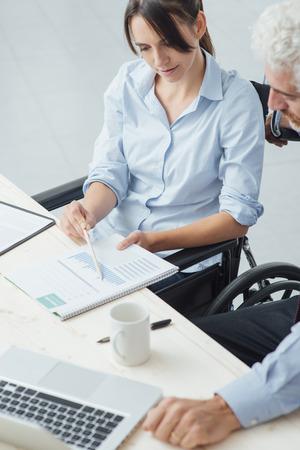 discapacidad: Mujer de negocios joven en silla de ruedas que trabaja en el escritorio de oficina y verificación de documentos con su colega concepto, la discapacidad y la independencia de sexo masculino