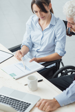 wheelchair: Young business woman on wheelchair working at office desk and checking paperwork with her male colleague, disability and independence concept Stock Photo