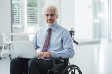 hombre de negocios: Successful corporate businessman in wheelchair at office using a laptop and working