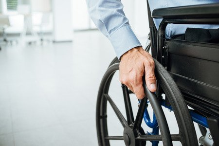 moving office: Businessman in wheelchair, hand on wheel close up, office interior on background