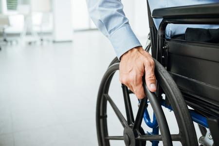 Zakenman in een rolstoel, met de hand op het wiel close-up, kantoor interieur op de achtergrond