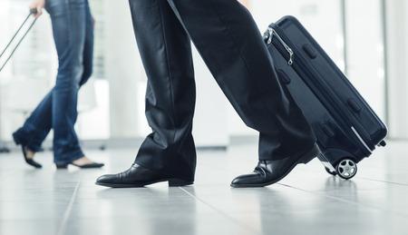 Passagiers lopen op de terminal met bagage en trolley, onherkenbare mensen Stockfoto
