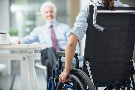 personas discapacitadas: Mujer lisiada tener una reuni�n de negocios con una visi�n de negocios detr�s, enfoque selectivo