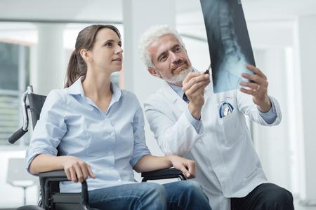 fractura: Radiólogo examina a una mujer en la radiografía de la silla de ruedas de la columna vertebral humana durante una visita en el hospital