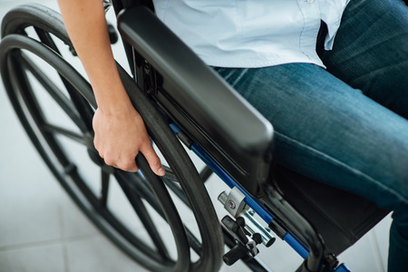 Woman in wheelchairs hand on wheel close up, disability and handicap concept