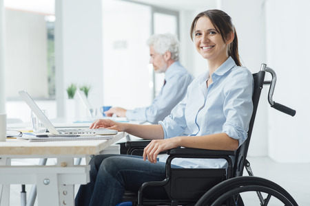 young office workers: Confident happy businesswoman in wheelchair working at office desk and using a laptop, she is smiling at camera, disability overcoming concept