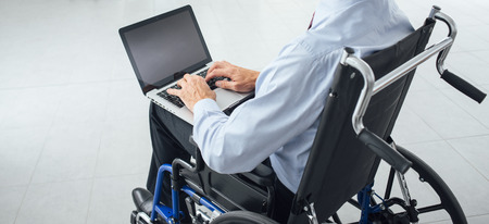 Corporate businessman in wheelchair using a laptop and networking, unrecognizable person