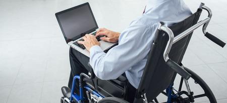 Corporate zakenman in rolstoel met behulp van een laptop en netwerken, onherkenbaar persoon