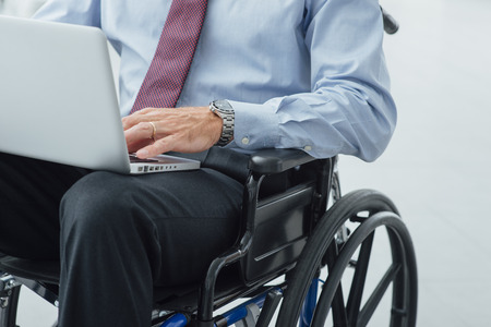 unrecognizable person: Corporate businessman in wheelchair using a laptop and networking, unrecognizable person