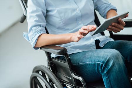 paraplegico: mujer irreconocible en silla de ruedas con un concepto de tableta de pantalla táctil, la discapacidad y la asistencia digitales