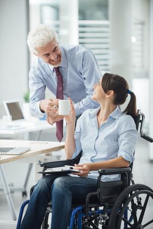 paraplegic: Hombre de negocios dando una taza de café a su compañera de trabajo inhabilitado durante un descanso en la oficina, la asistencia y el concepto de la amistad Foto de archivo