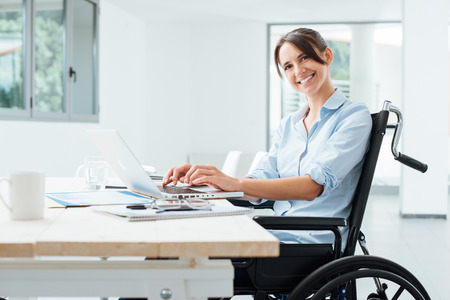 career woman: Confident happy businesswoman in wheelchair working at office desk and using a laptop, she is smiling at camera, disability overcoming concept