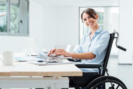 Vertrouwen gelukkig zakenvrouw in een rolstoel werken op kantoor en het gebruik van een laptop, is ze glimlachend op camera, handicap overwinnen van begrip