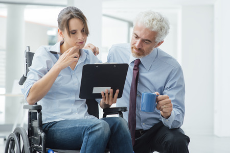 Businessman showing a document on a clipboard to a young woman in wheelchair, assistance and help concept Standard-Bild