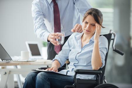 persona en silla de ruedas: Mujer de negocios en silla de ruedas que tiene un dolor de cabeza en la oficina, su colega le está dando un vaso de agua y ayudándola