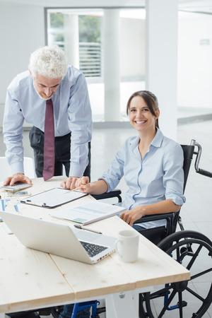 paraplegico: Mujer de negocios confidente en silla de ruedas que trabaja en el escritorio de oficina con su colega masculino y sonriendo a la cámara