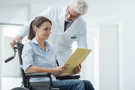 physical impairment: Doctor and patient examining a file with medical records, she is sitting on a wheelchair, assistance and health care concept