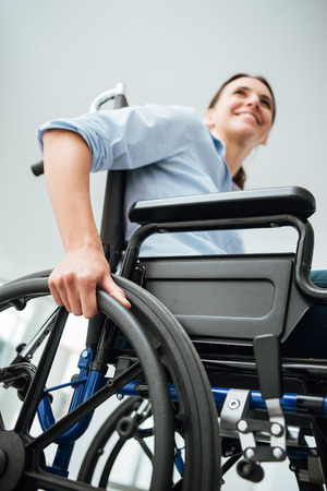 Young woman in wheelchair smiling and looking away, disability concept