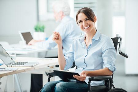 discapacidad: Oficinista de sexo femenino feliz en la celebraci�n de un portapapeles y sonriendo a la c�mara en silla de ruedas, personas con discapacidad apoyan en el lugar de trabajo
