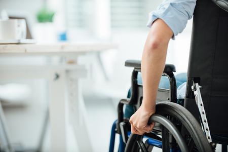 discapacidad: Mujer en silla de ruedas junto a un escritorio de oficina, la mano de cerca, persona irreconocible