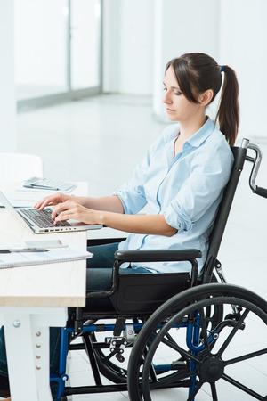 discapacidad: Mujer de negocios joven con discapacidad en silla de ruedas que trabaja en el mostrador de la oficina y escribiendo en un concepto de ordenador portátil, la accesibilidad y la independencia Foto de archivo