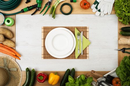 table set: Gardening tools and fresh vegetables composing a frame, table set at center with dish, fork and knife, top view