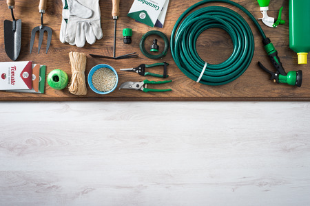 Gardening and farming tools on a wooden table with blank copy space, top view