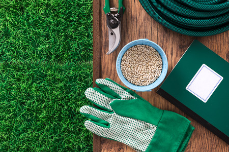 Farming and home gardening tools with green grass and farming manual book guide, top view