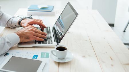 전문 사업가 사무실 책상에서 일하고와 노트북에 입력, 인식 할 수없는 사람