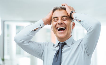 careless: Cheerful careless businessman laughing and touching his forehead