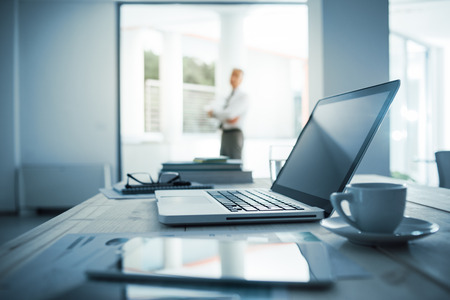 recursos humanos: El hombre de negocios de pie con los brazos cruzados en su oficina, escritorio con ordenador port�til en primer plano, atenci�n selectiva