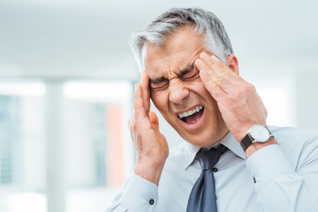 soreness: Suffering businessman having a terrible headache and touching his temples, stress and illness concept Stock Photo