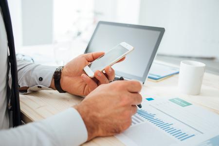 Geschäftsmann am Schreibtisch mit einem Finanz App auf seinem Smartphone und arbeitet an Berichten, die Hände Nahaufnahme