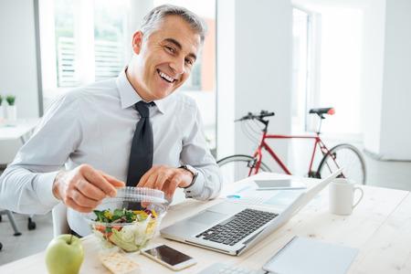 almuerzo: Hombre de negocios feliz abriendo su mochila ensalada y tener un descanso para comer en el escritorio de oficina