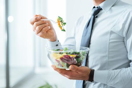 hombre comiendo: De negocios que tiene una ensalada de verduras para el almuerzo, la alimentación saludable y estilo de vida concepto, persona irreconocible
