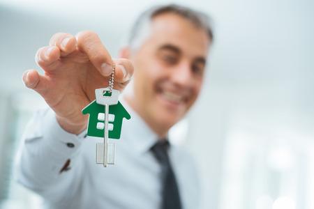 Zelfverzekerd makelaar houden van uw nieuwe huis sleutels en glimlachen op camera Stockfoto