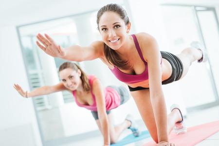 gimnasio: Mujeres jóvenes deportivo en el gimnasio haciendo ejercicios de pilates en una estera, la aptitud y el concepto de estilo de vida saludable