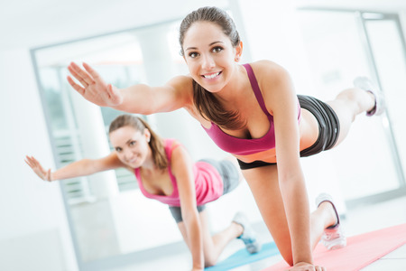 workout: Sporty young women at the gym doing pilates workout on a mat, fitness and healthy lifestyle concept