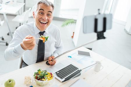 empresario: Hombre de negocios sonriendo feliz en el escritorio de oficina tener un descanso para almorzar y tomar selfies con un palo selfie y un tel�fono inteligente