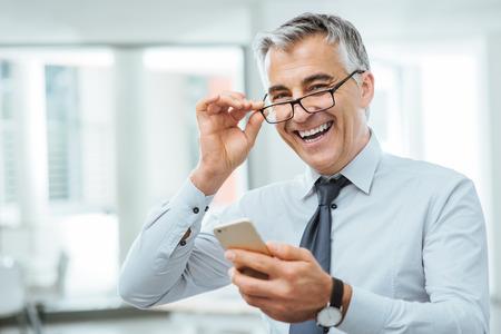 Lachend zakenman met gezichtsproblemen, hij is het aanpassen van zijn bril en iets op zijn mobiele telefoon lezen