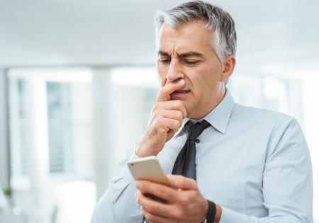 confundido: Hombre de negocios confuso con la mano en la barbilla teniendo problemas usando un teléfono inteligente