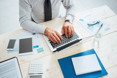 mecanografía: Hombre de negocios profesional que trabaja en el mostrador de la oficina y escribiendo en un ordenador portátil, persona irreconocible Foto de archivo