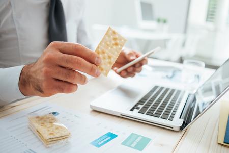 Zakenman met een snack bij bureau met een kraker en een slimme telefoon, handen close-up, onherkenbaar persoon Stockfoto